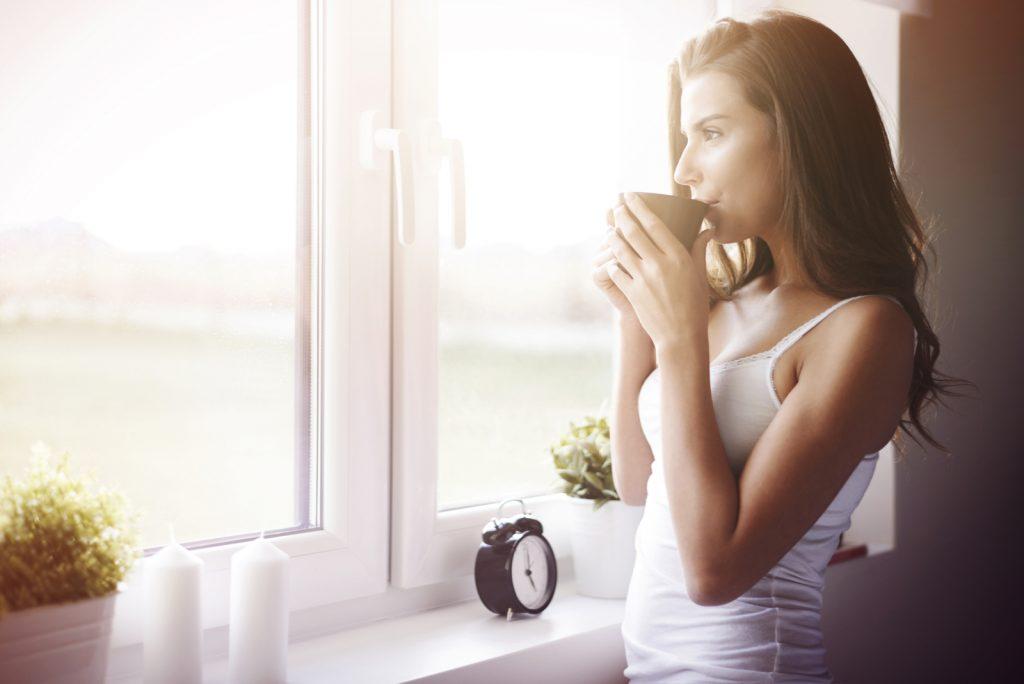 kvinde stående ved vinduet