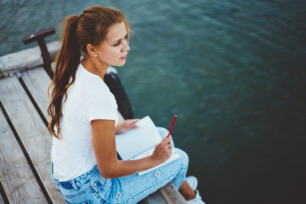 kvindelig kunstner, der hviler på mole nær floden