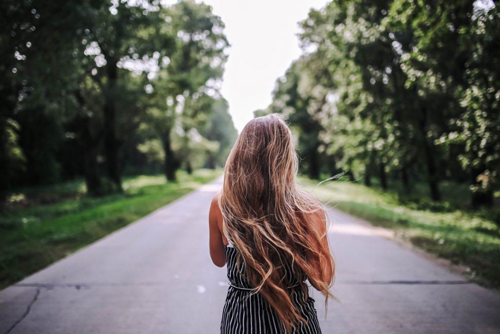 langhåret ung kvinde går langs vejen mellem skoven