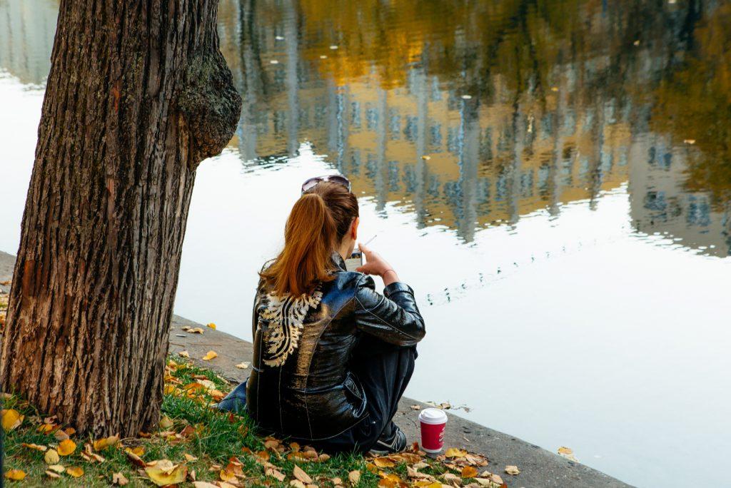 pige i efteråret park nær vandet