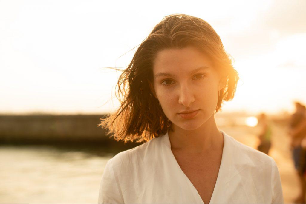 pige i en hvid skjorte ved solnedgang blæser vinden