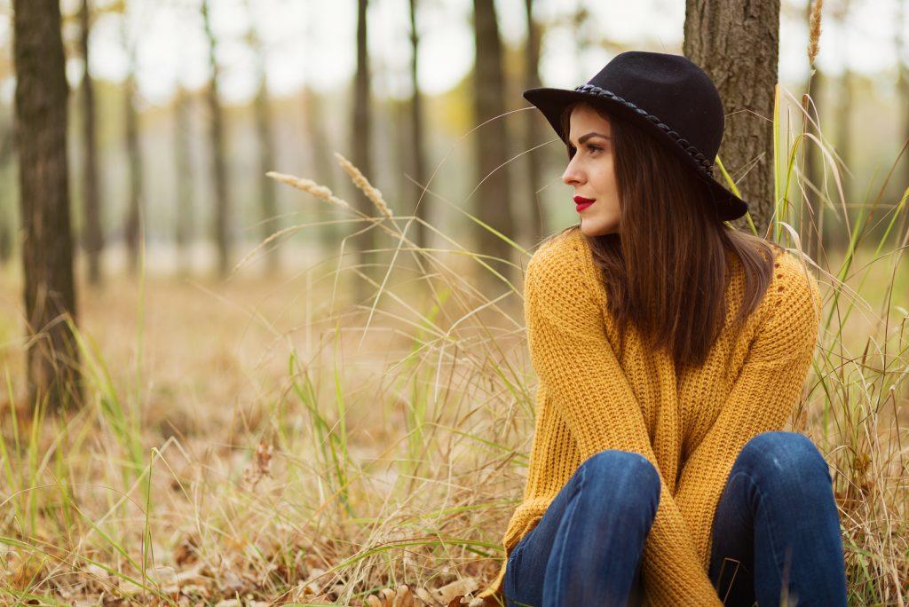 pige sidder i efterårsskoven