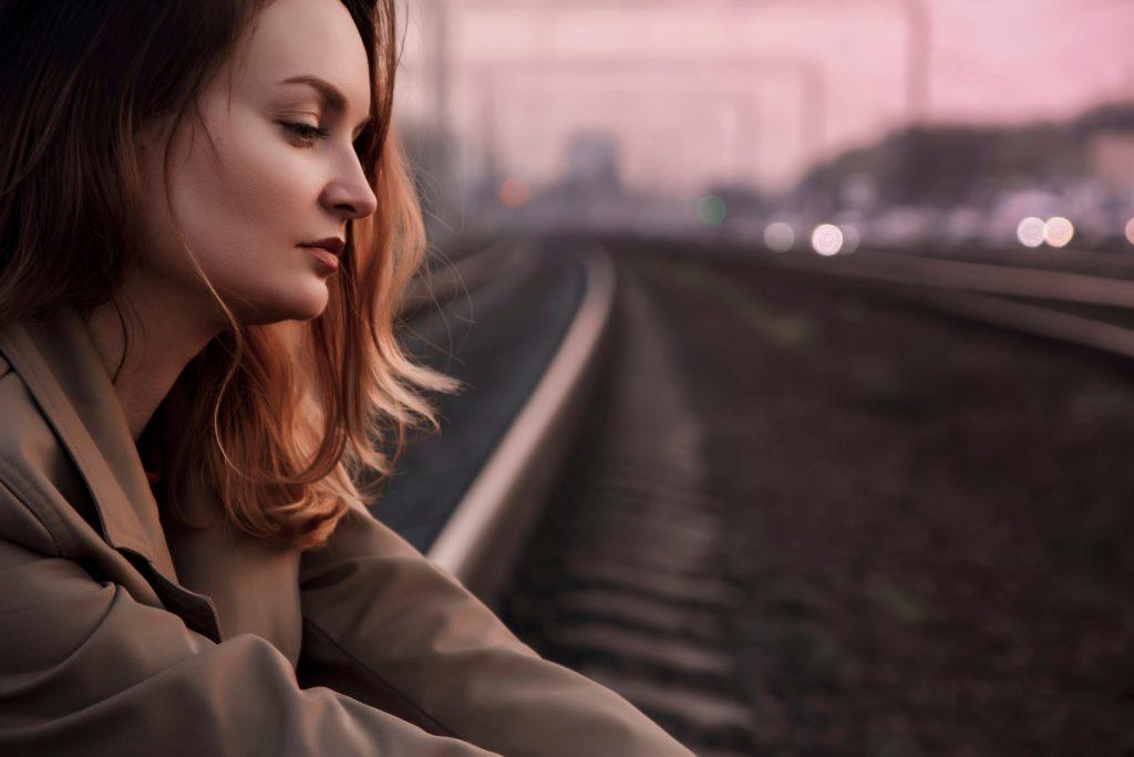 pige sidder på en jernbane i solnedgangens stråler