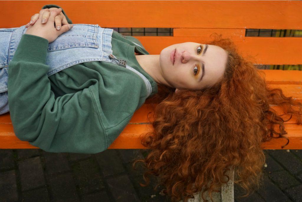 rødhåret kvinde liggende på orange bænk i solrig efterårsdag