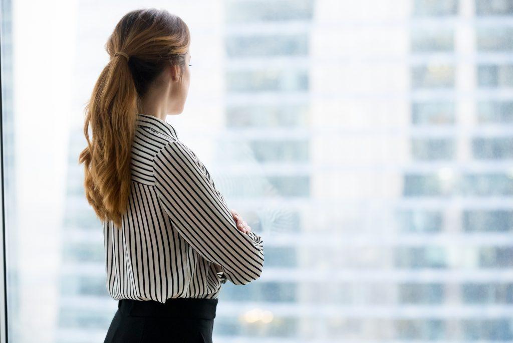selvsikker rig forretningskvinde ser frem gennem glas