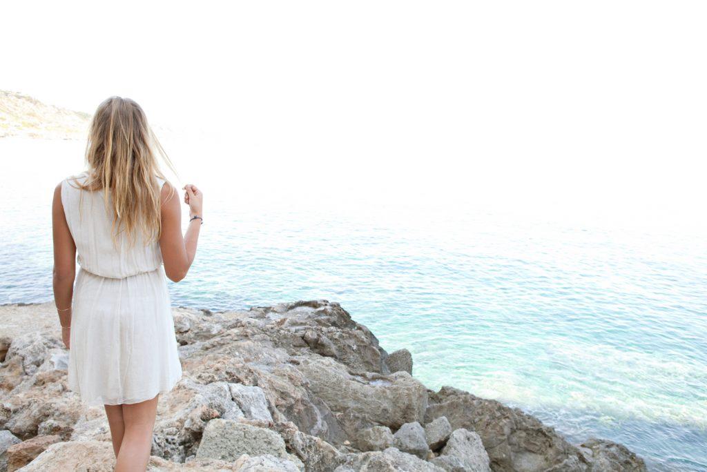 smuk ung blond kvinde på en stenet strand