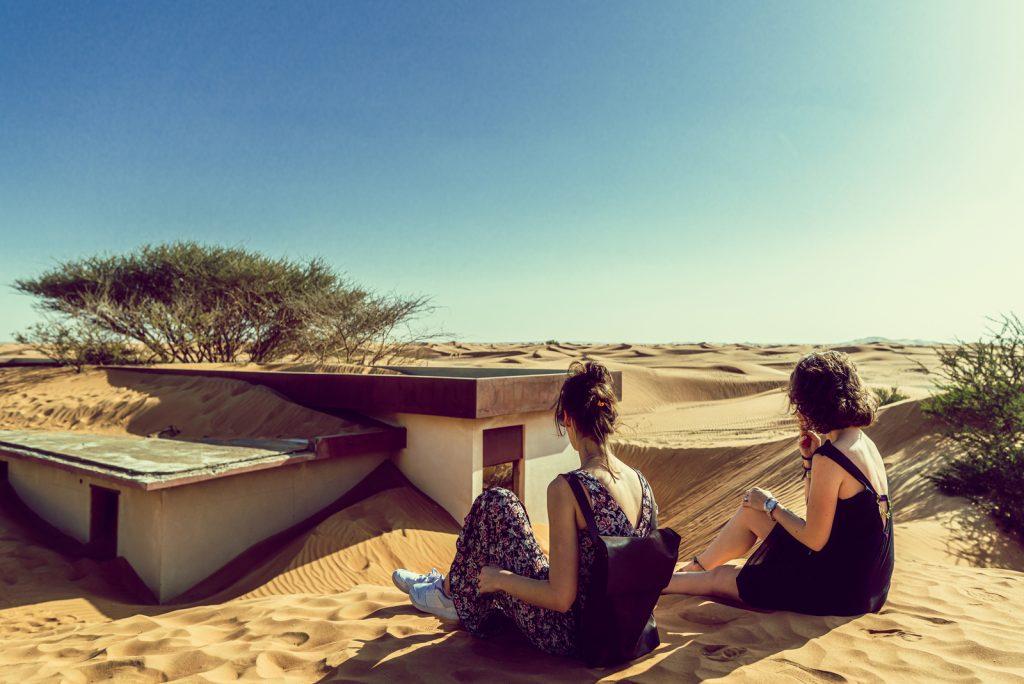 to kvindelige venner sidder i ørkenen