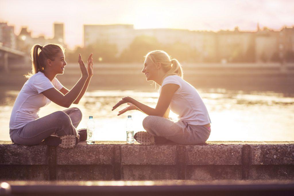to kvindelige venner sidder udendørs