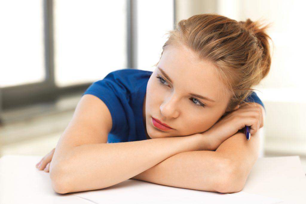 træt teenagepige med pen og papir