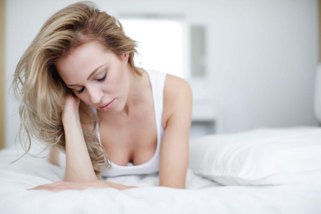 trist kvinde, der ligger i sengen