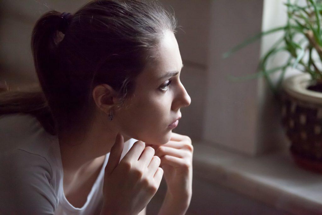 ung kvinde ser langt i vinduetænkning